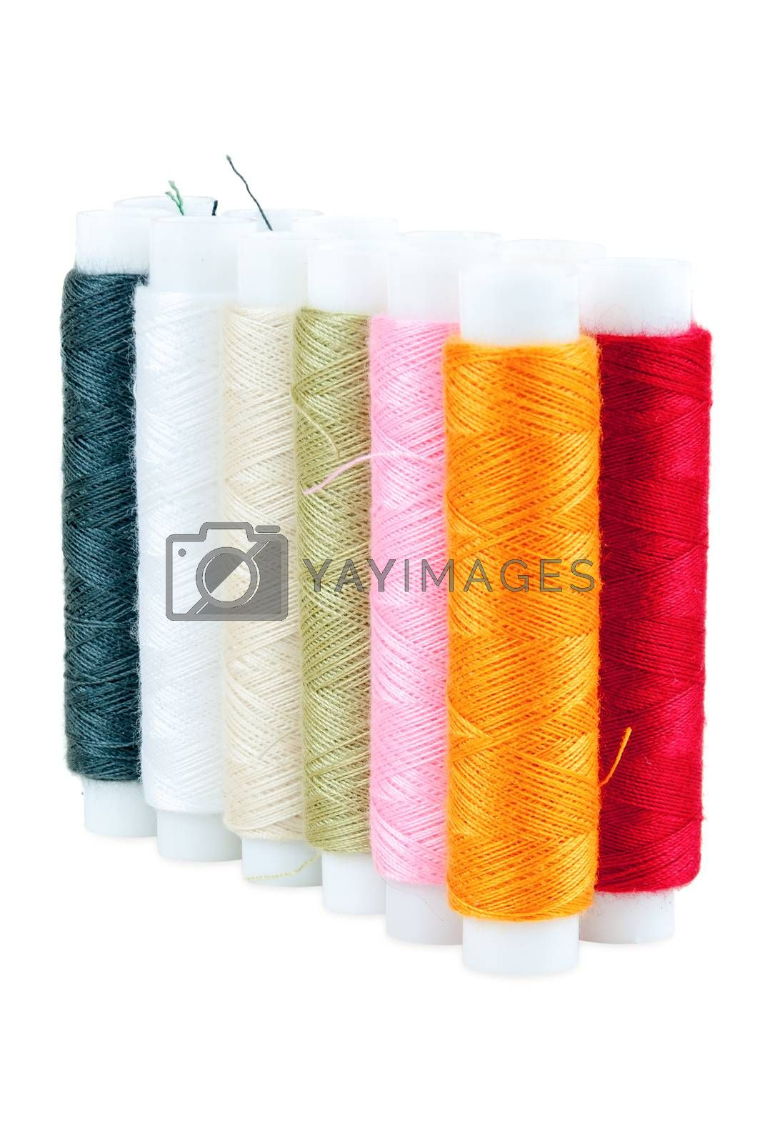 Colored spools of threads on white background by mkos83