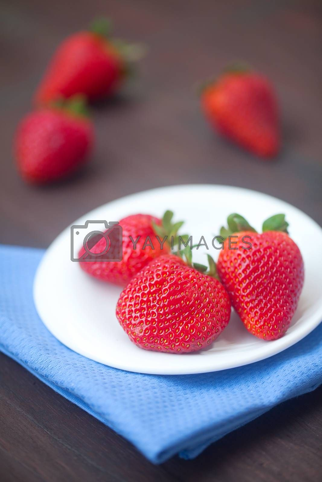 red juicy strawberry in a plate on a wooden surface by jannyjus