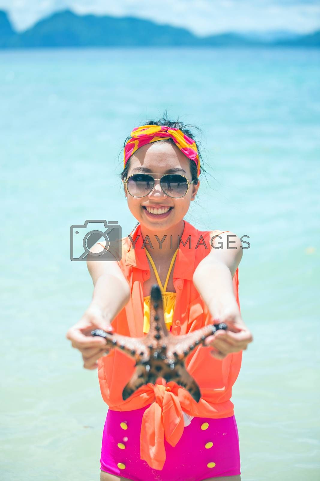Young woman shows starfish during holiday at tropical island by jakgree
