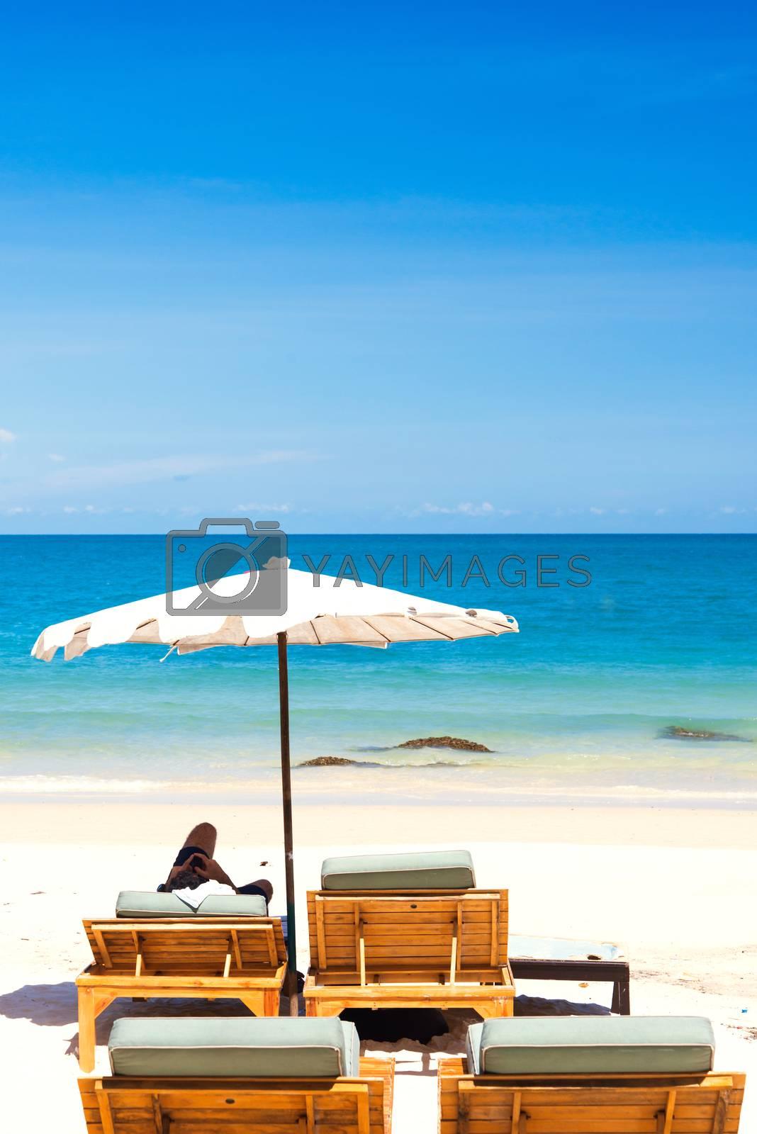 Beach chair and umbrella on sand beach. by jakgree