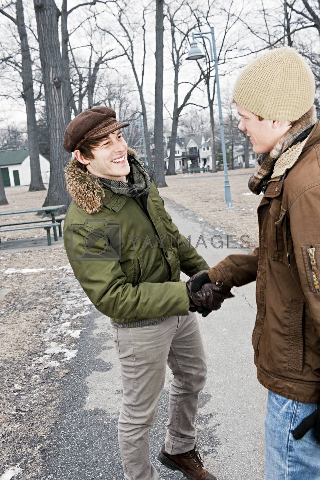 Two young men meeting in winter park shaking hands