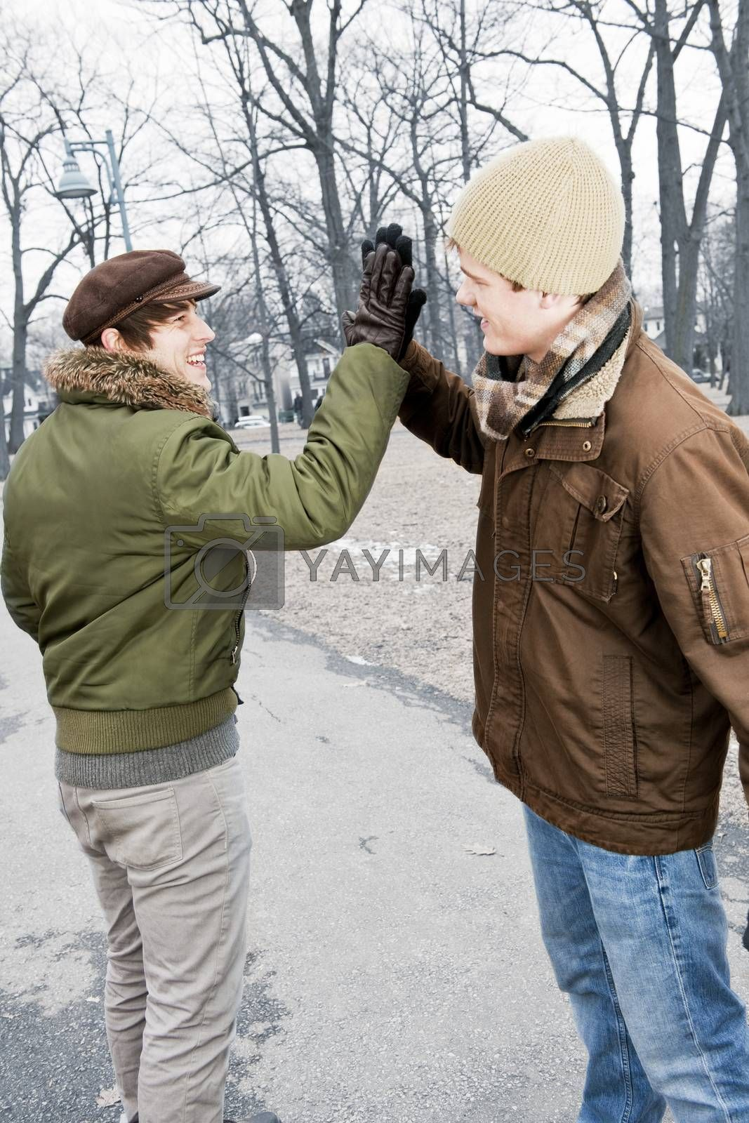 Two young men meeting in winter park giving high five
