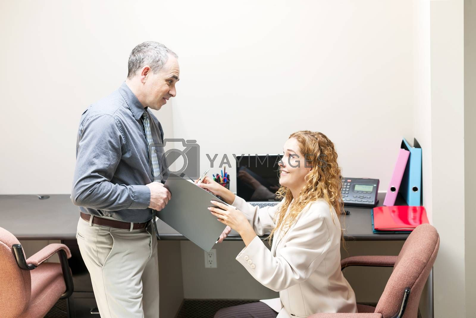 Man and woman meeting to discuss paperwork in office