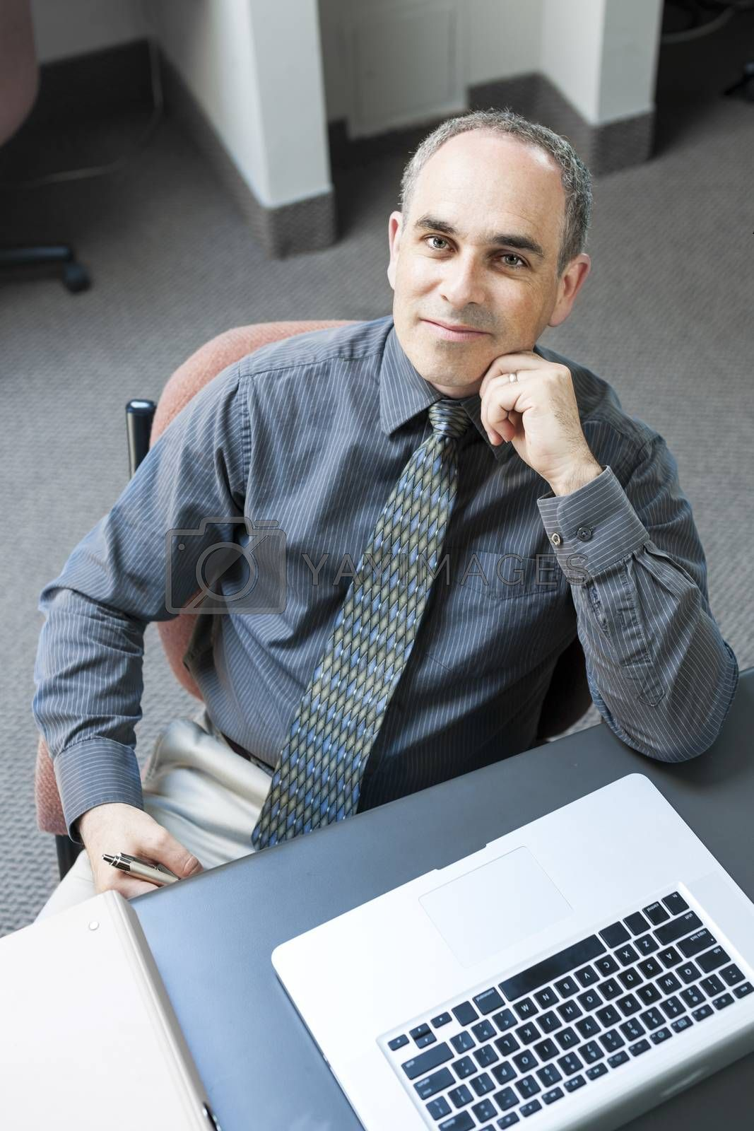 Businessman with laptop computer sitting at office workstation