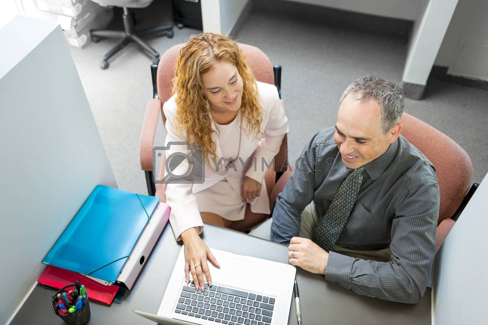 Man and woman sitting at desk with computer in office