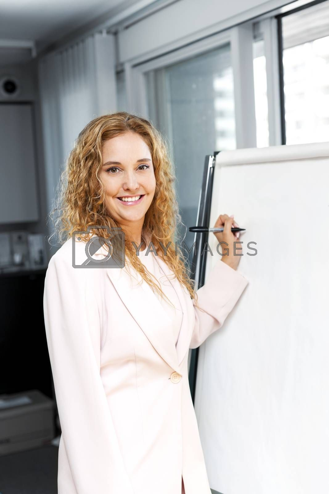 Smiling businesswoman writing on flip chart paper in office