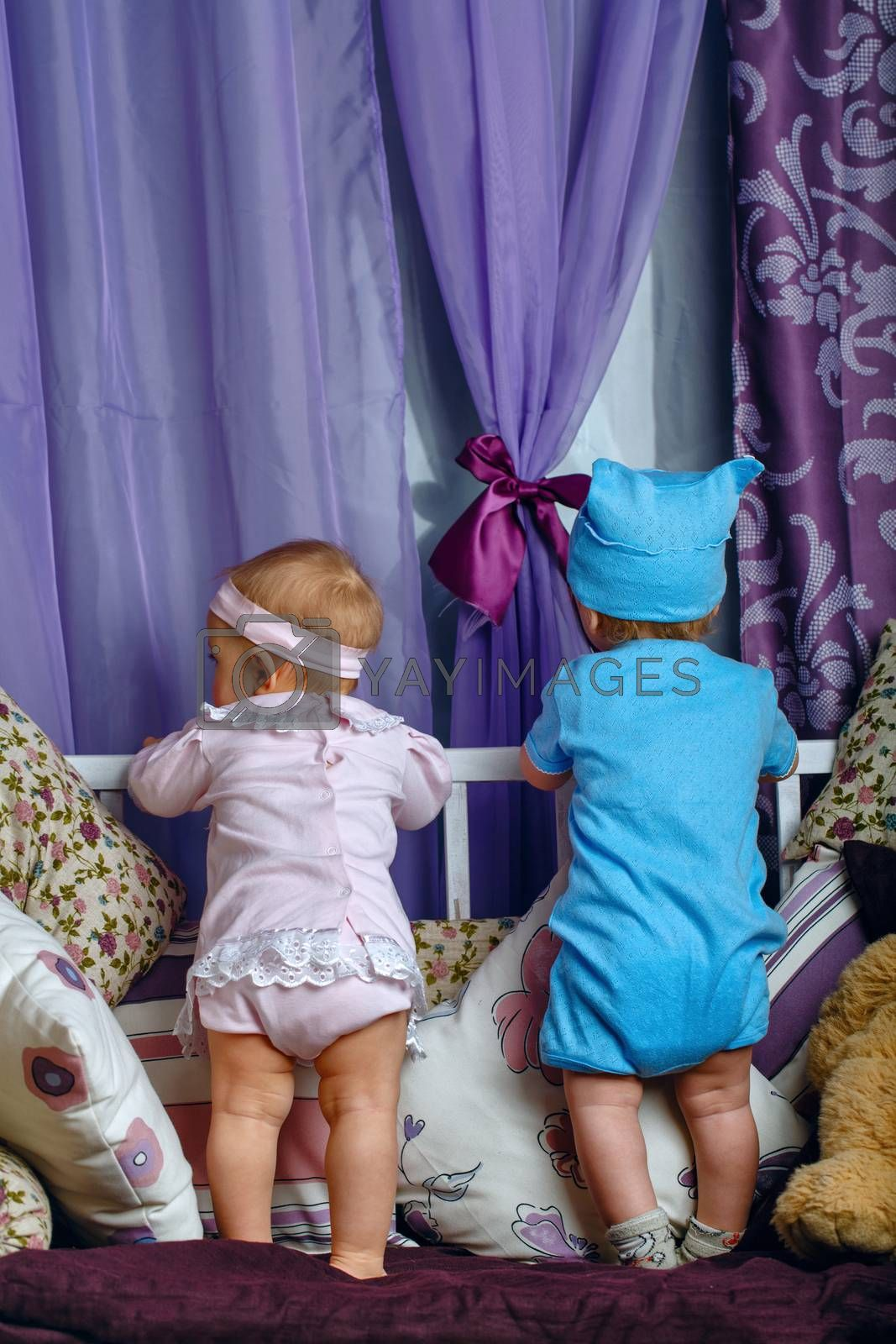 Brother and sister in the nursery are on the cradle turned to the window waiting for the arrival of parents