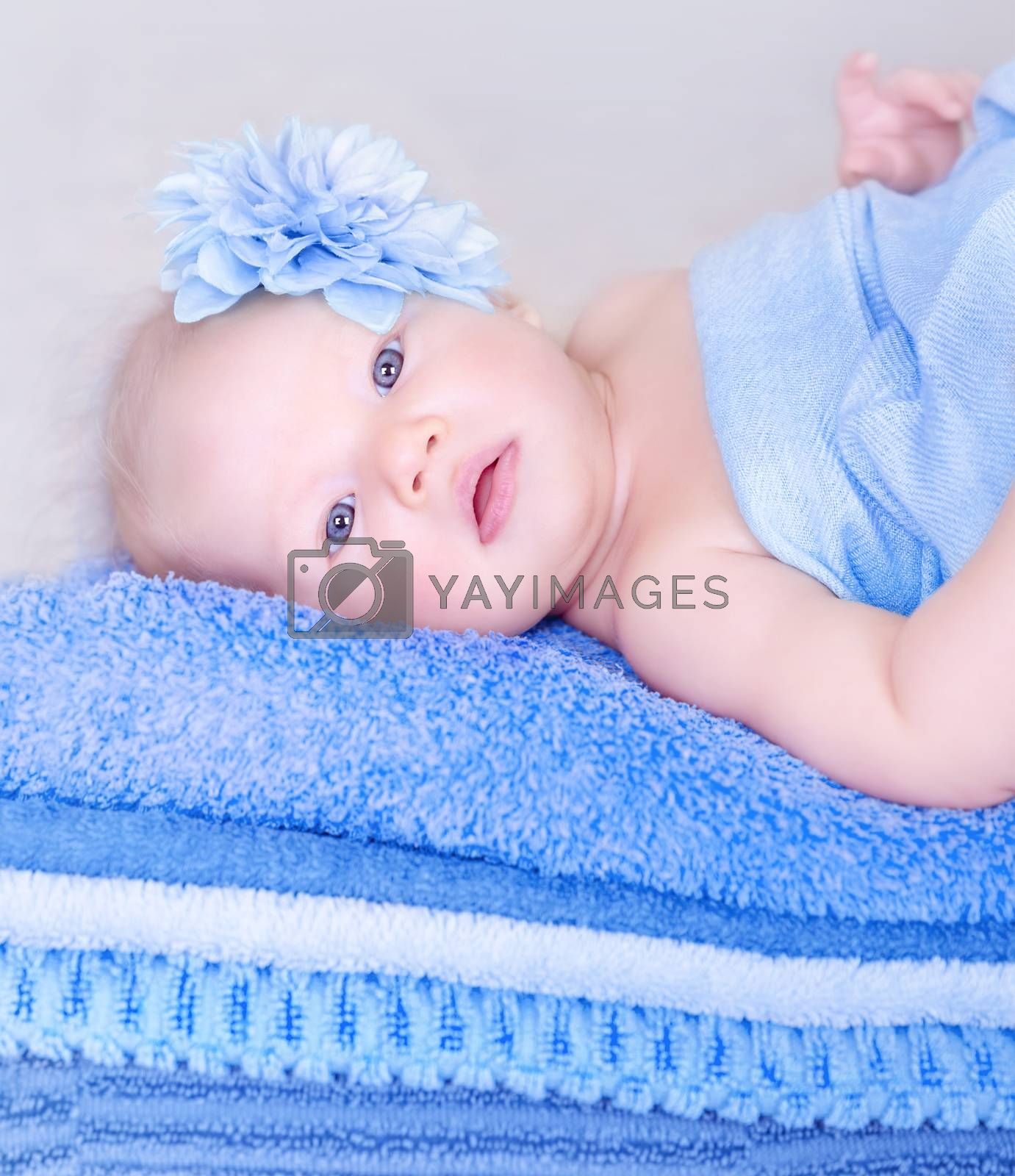 Closeup portrait of sweet newborn girl lying down on many soft blue towels, cute flower on head, innocence and tenderness concept