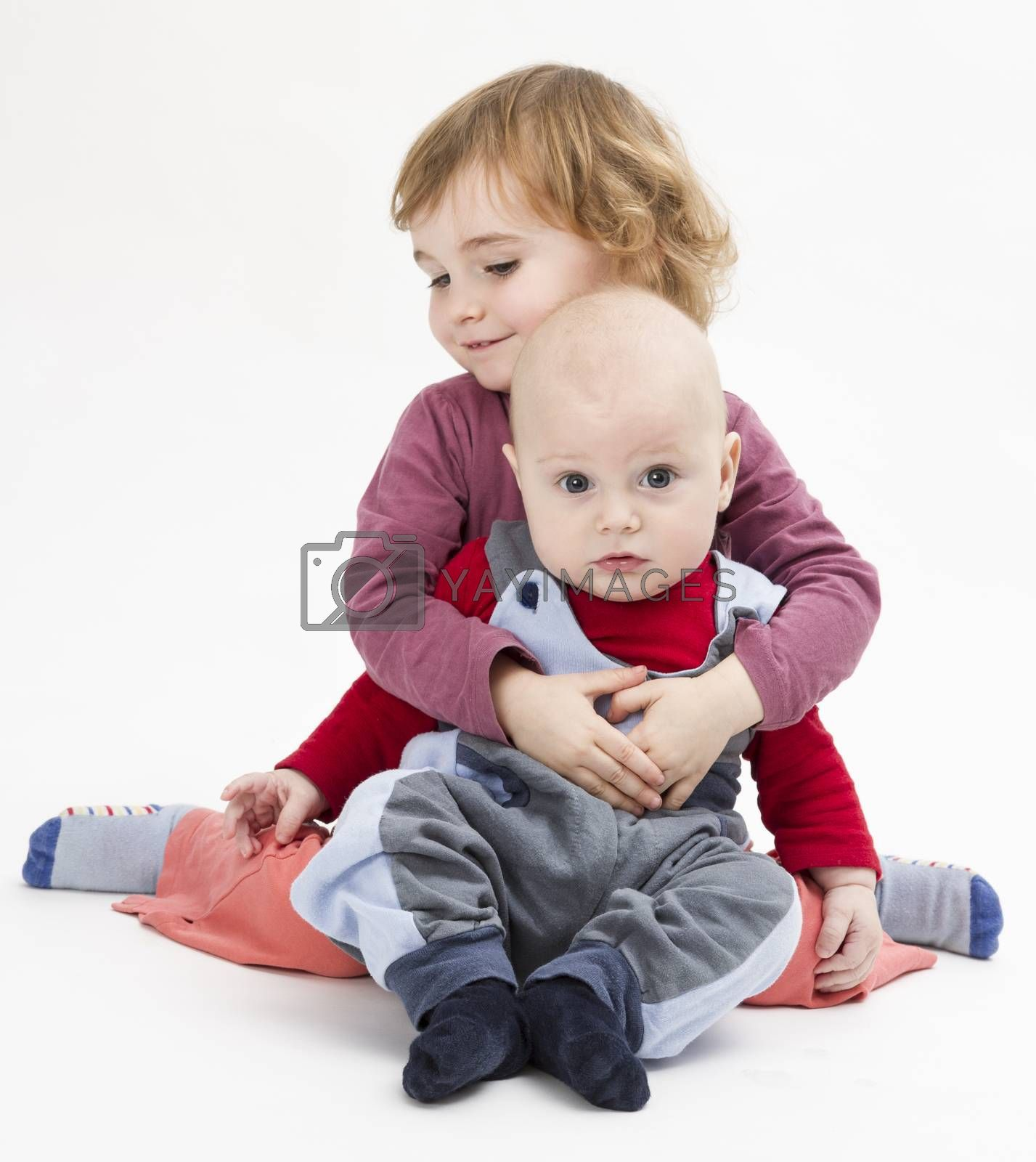 baby boy with 3 year old sister sitting in light background