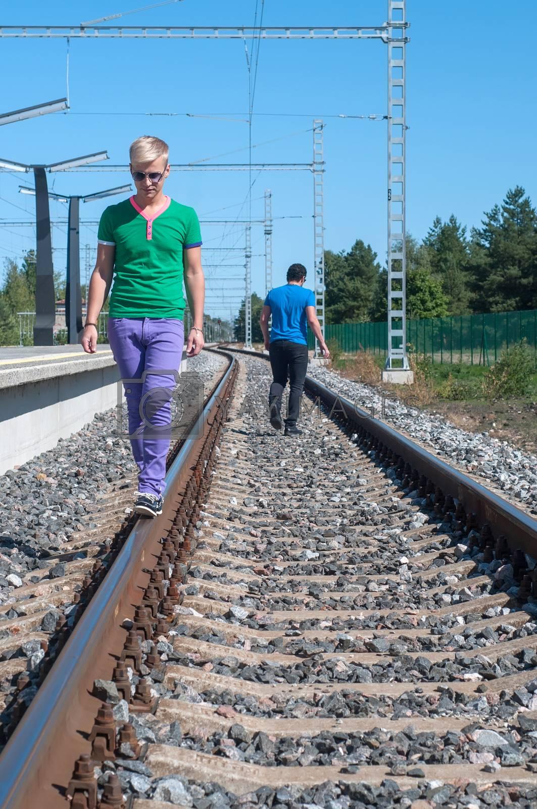 Shot of one man walking on train tracks