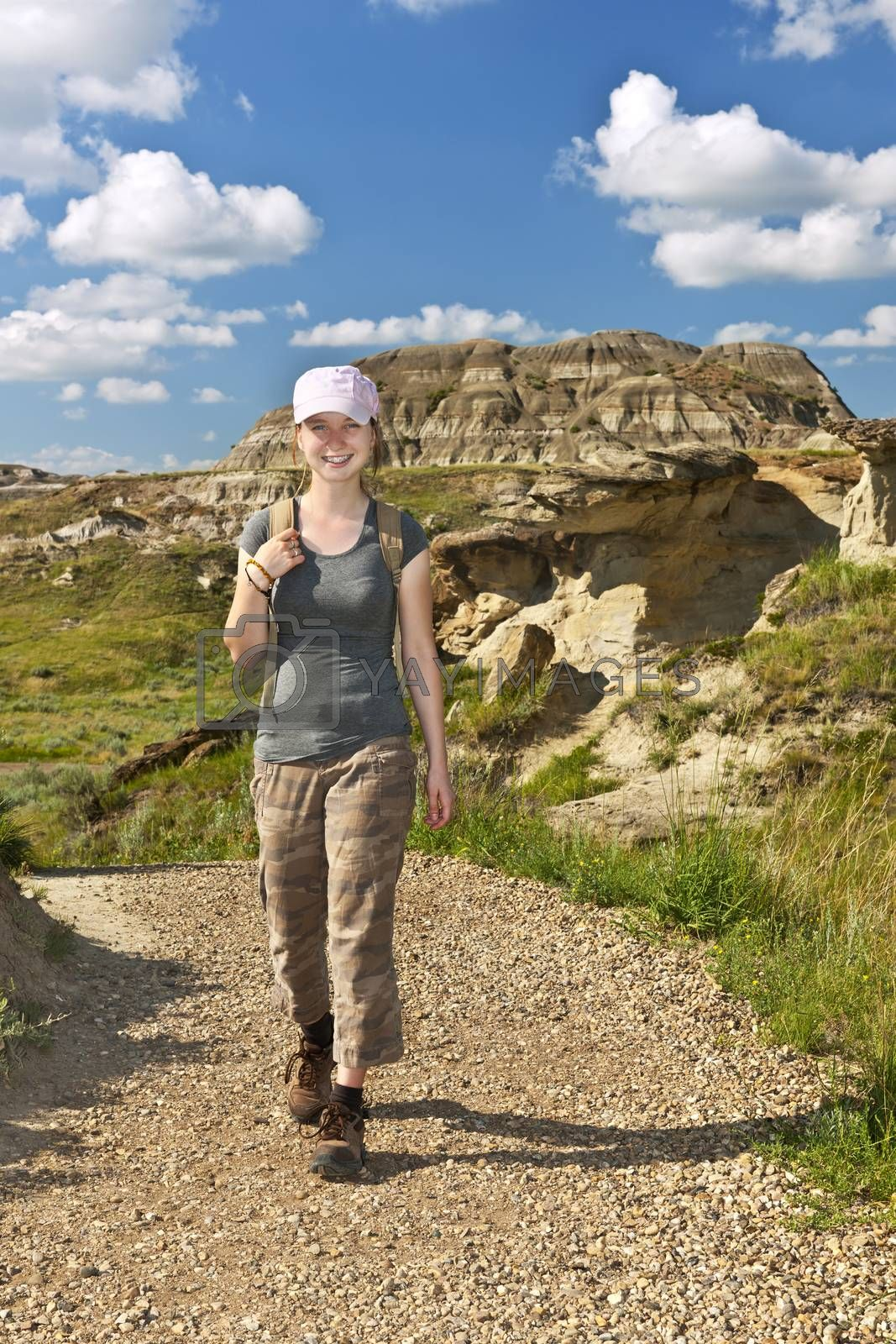 Smiling girl walking on path at the Badlands in Dinosaur provincial park, Alberta, Canada