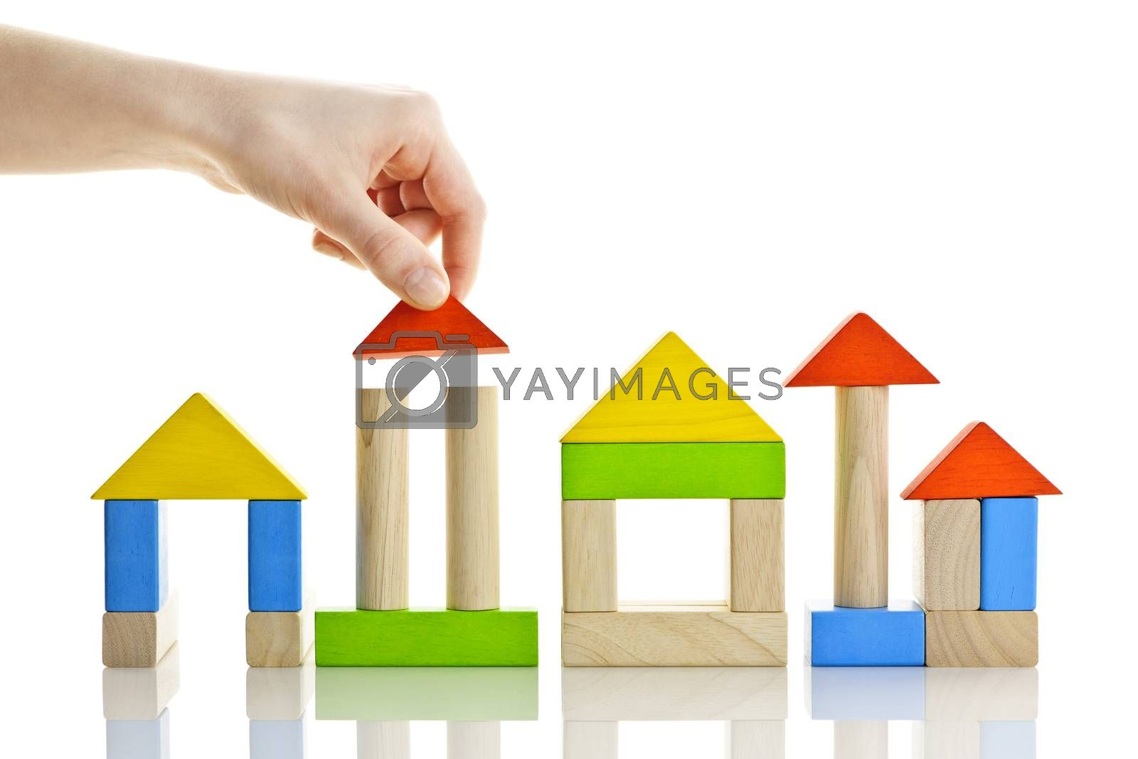 Hand building houses of wooden block toys isolated on white background