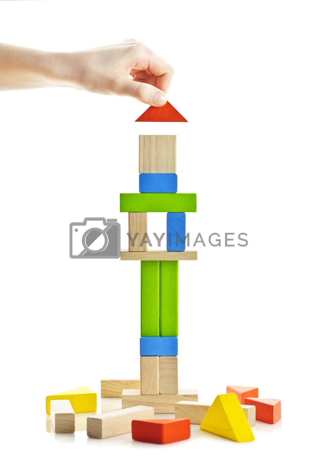 Hand building tower of wooden blocks isolated on white background