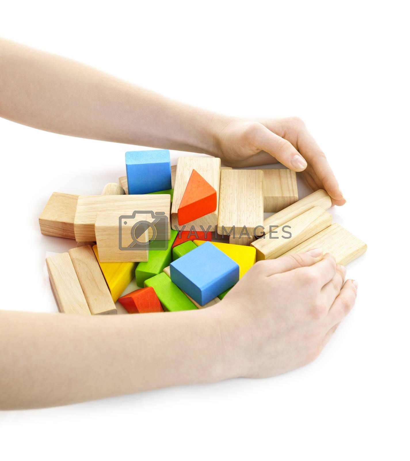 Hands gathering pile of wooden block toys isolated on white