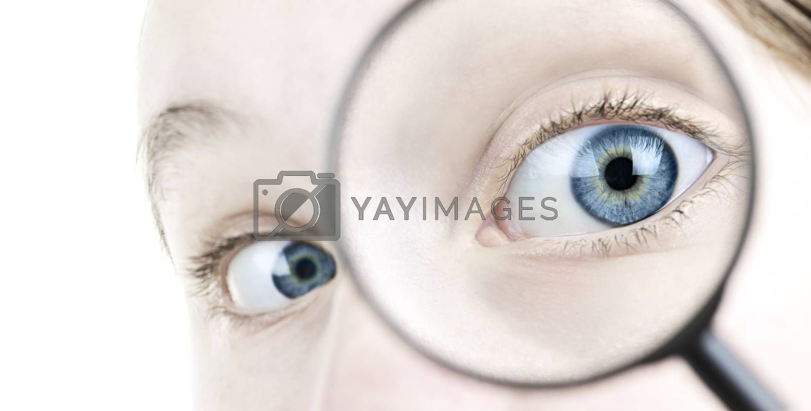 Female blue eye looking through magnifying glass close up
