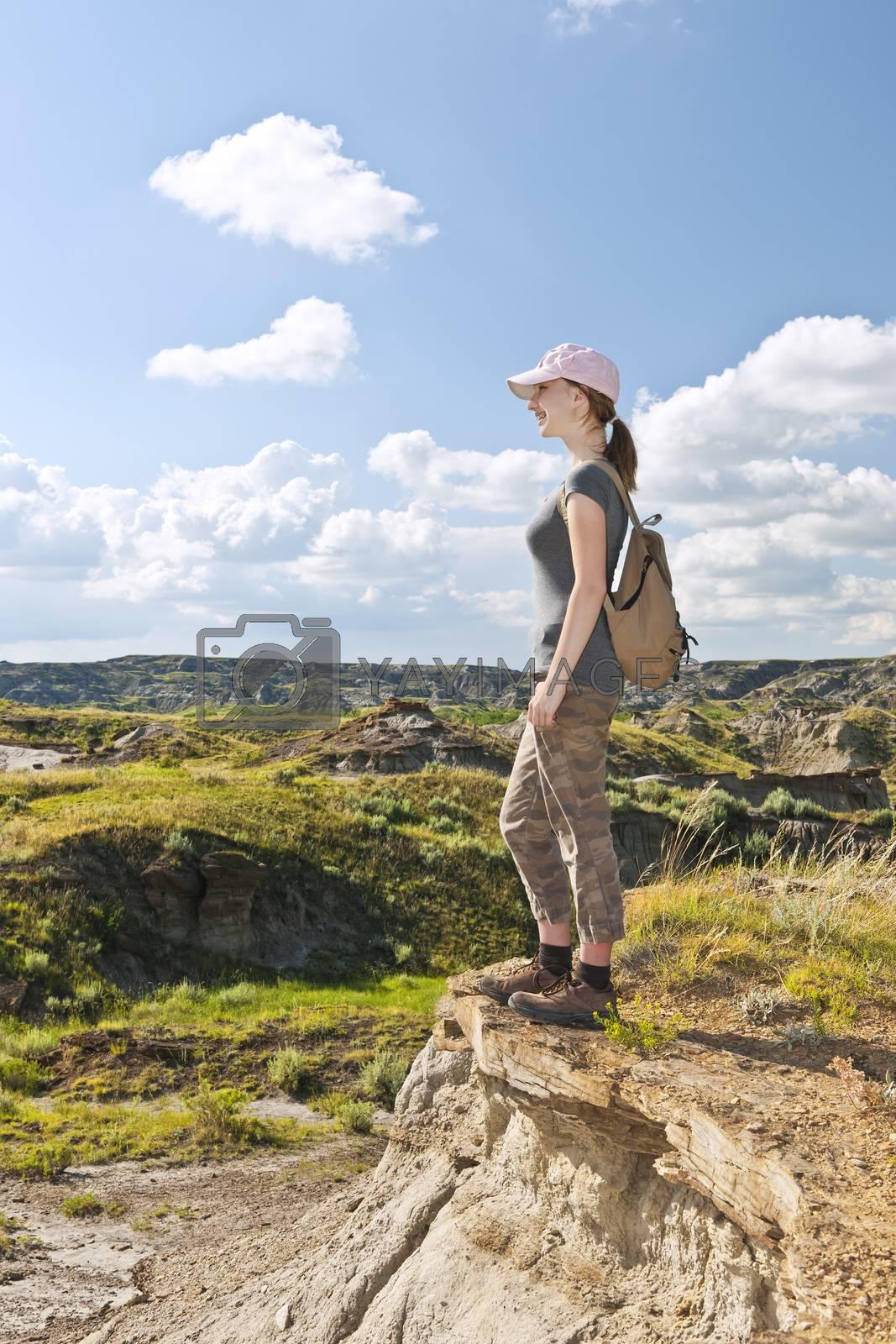 Happy female hiker looking onto the Badlands in Dinosaur provincial park, Alberta, Canada
