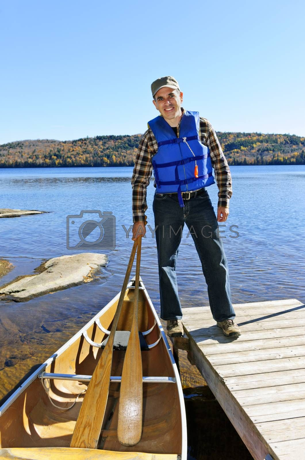 Man standing on dock with canoe on Lake of Two Rivers, Ontario, Canada