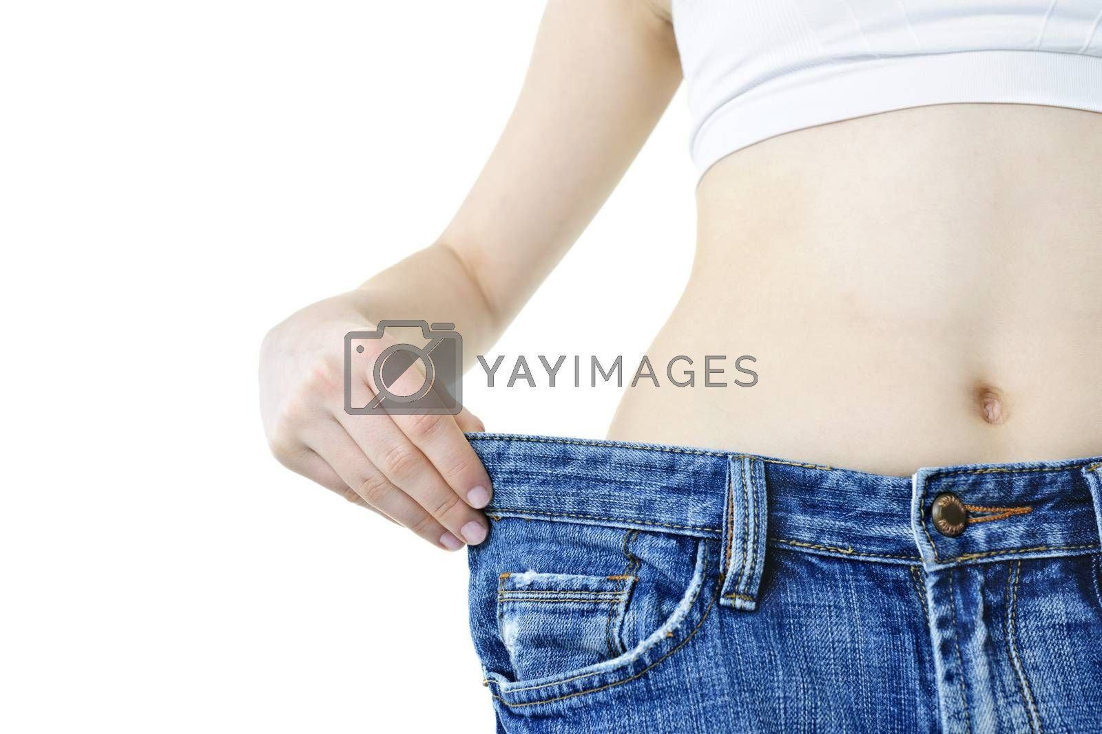 Fit young woman in loose jeans after losing weight isolated on white