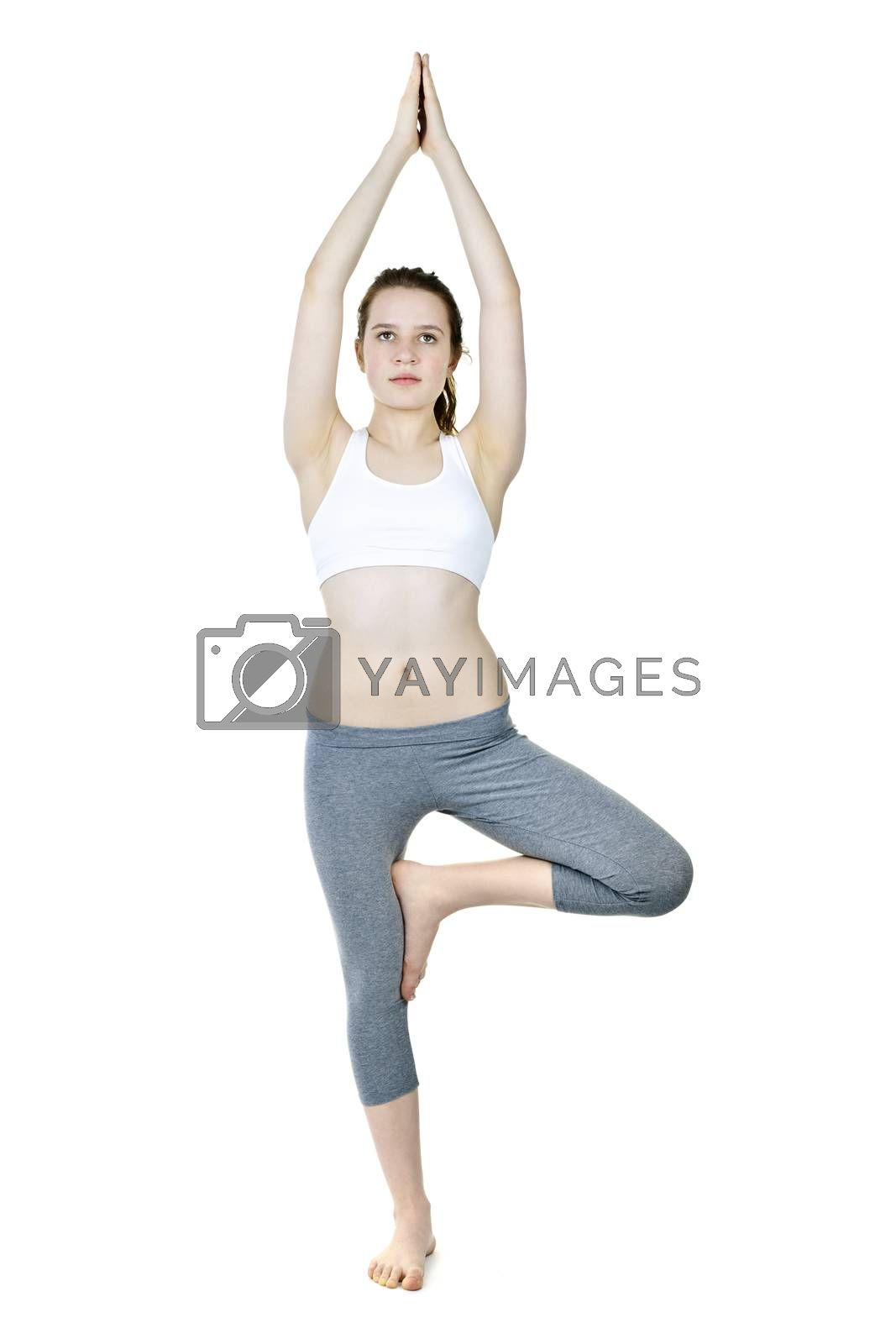 Healthy young woman doing tree yoga pose isolated on white