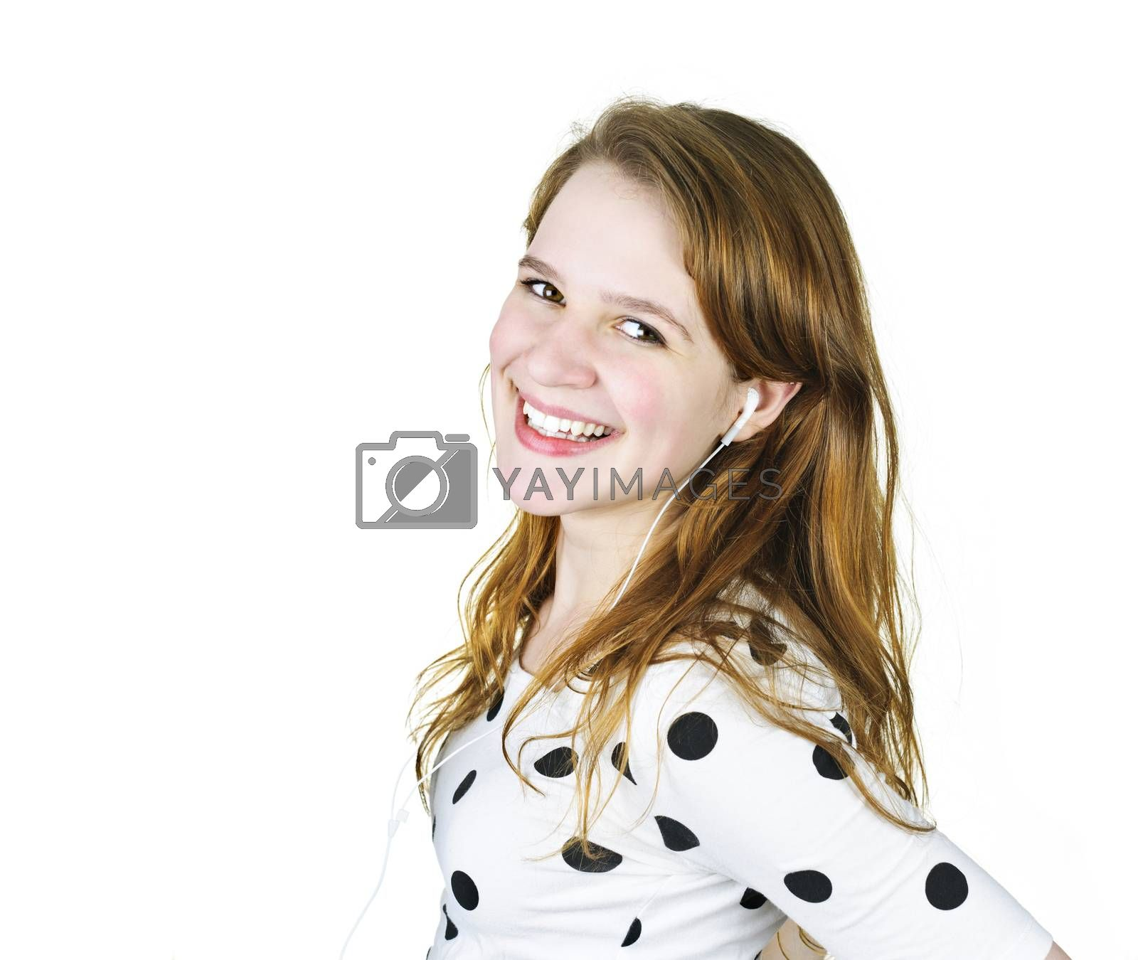 Isolated portrait of beautiful teenage girl listening to music with earphones