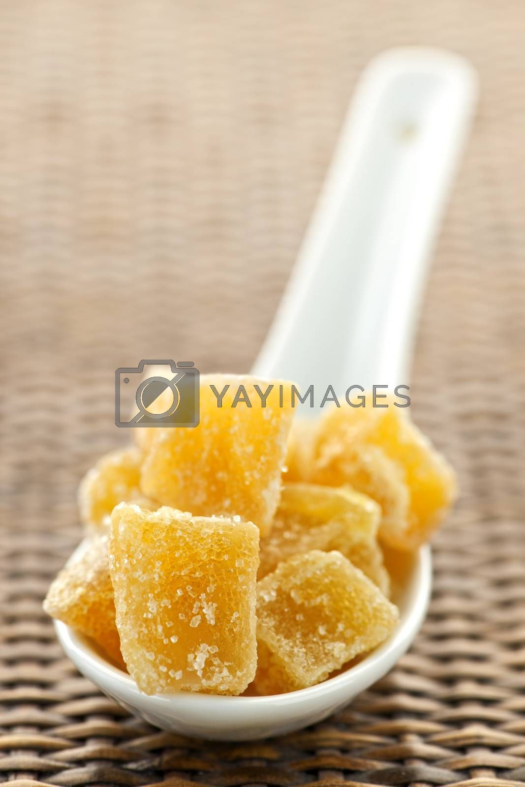Caramelized ginger candy pieces on white spoon close up