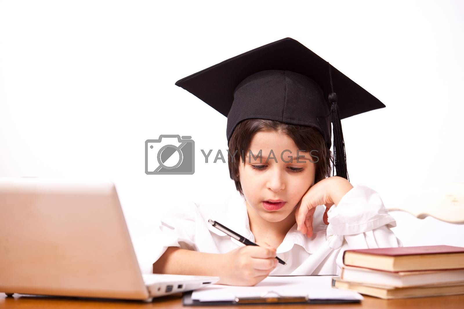 little boy in hat with computer and textbooks on white background writing on paper