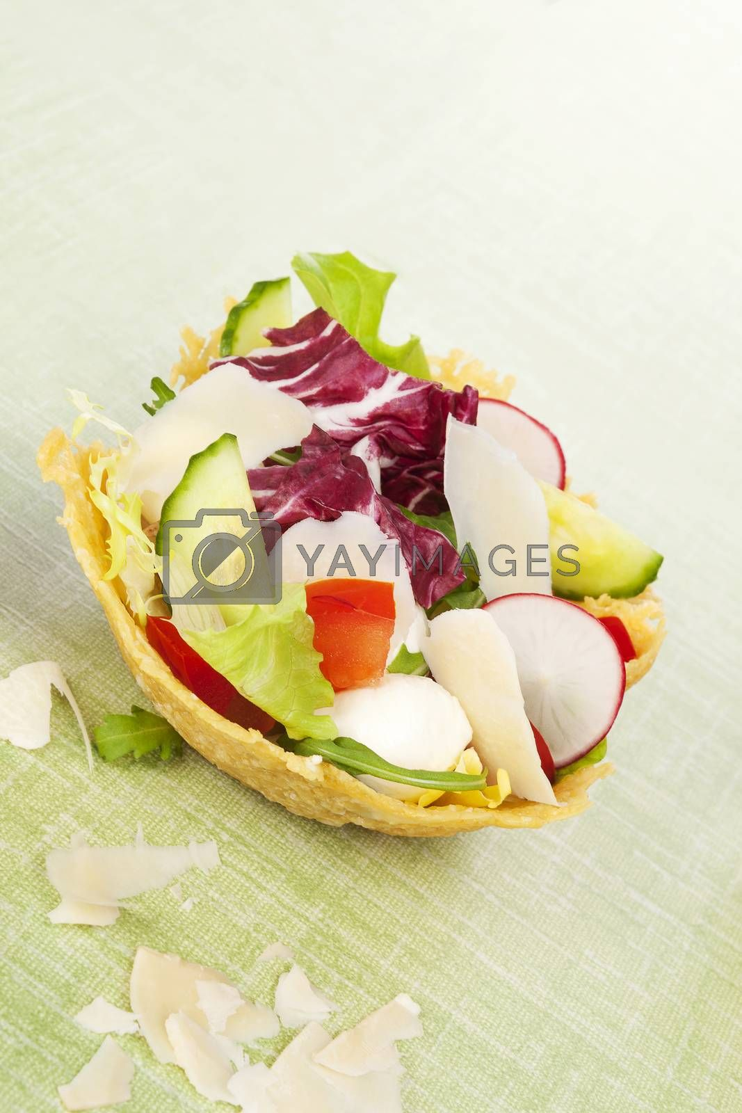 Cheese basket filled with fresh vegetable salad and bacon. Culinary eating.
