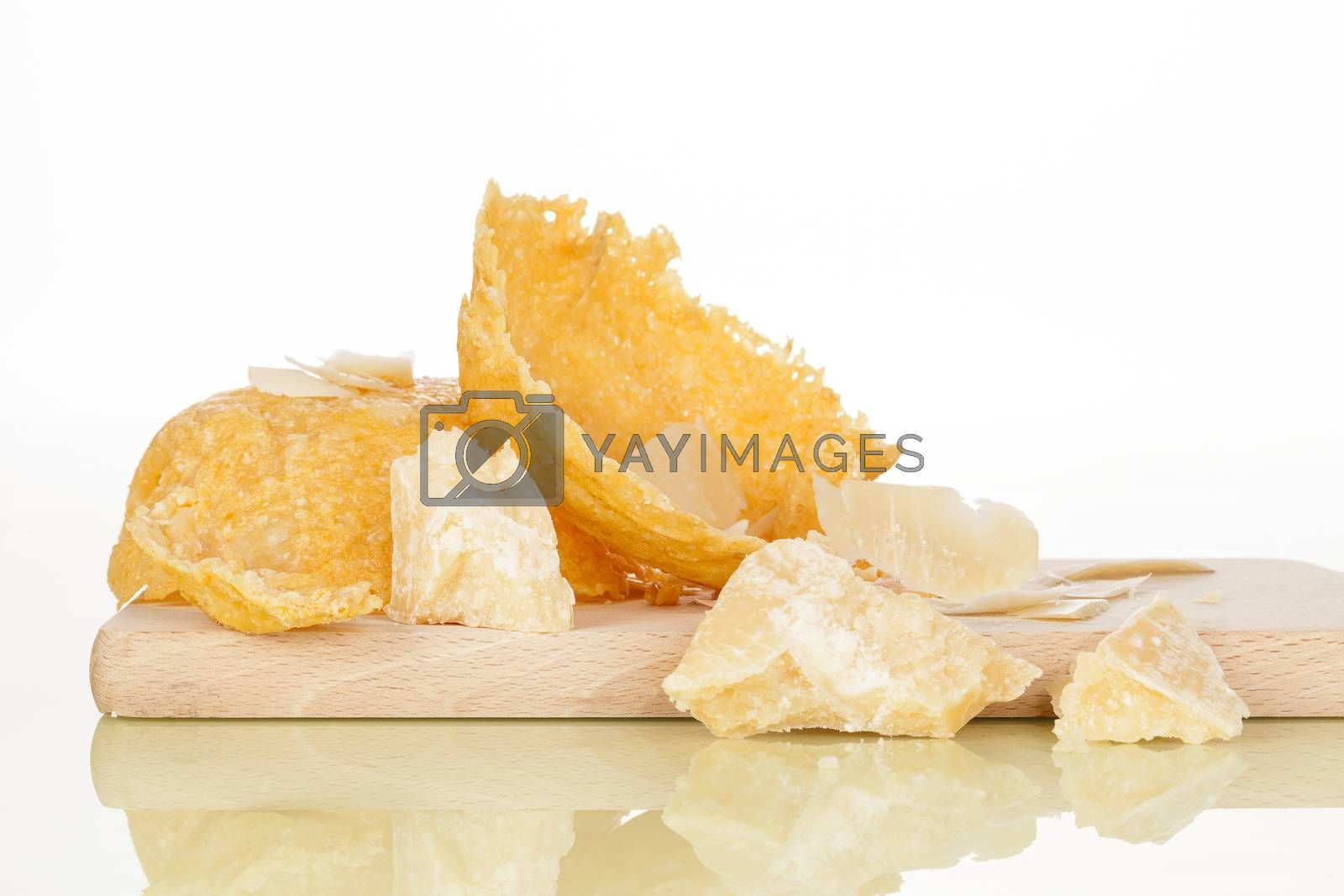 Parmigiano basked and parmigiano pieces on wooden kitchen board. Traditional parmigiano cheese eating.