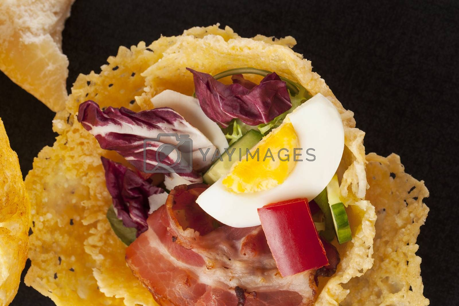 Parmigiano cheese basket filled with bacon and fresh vegetable. Culinary cheese eating.