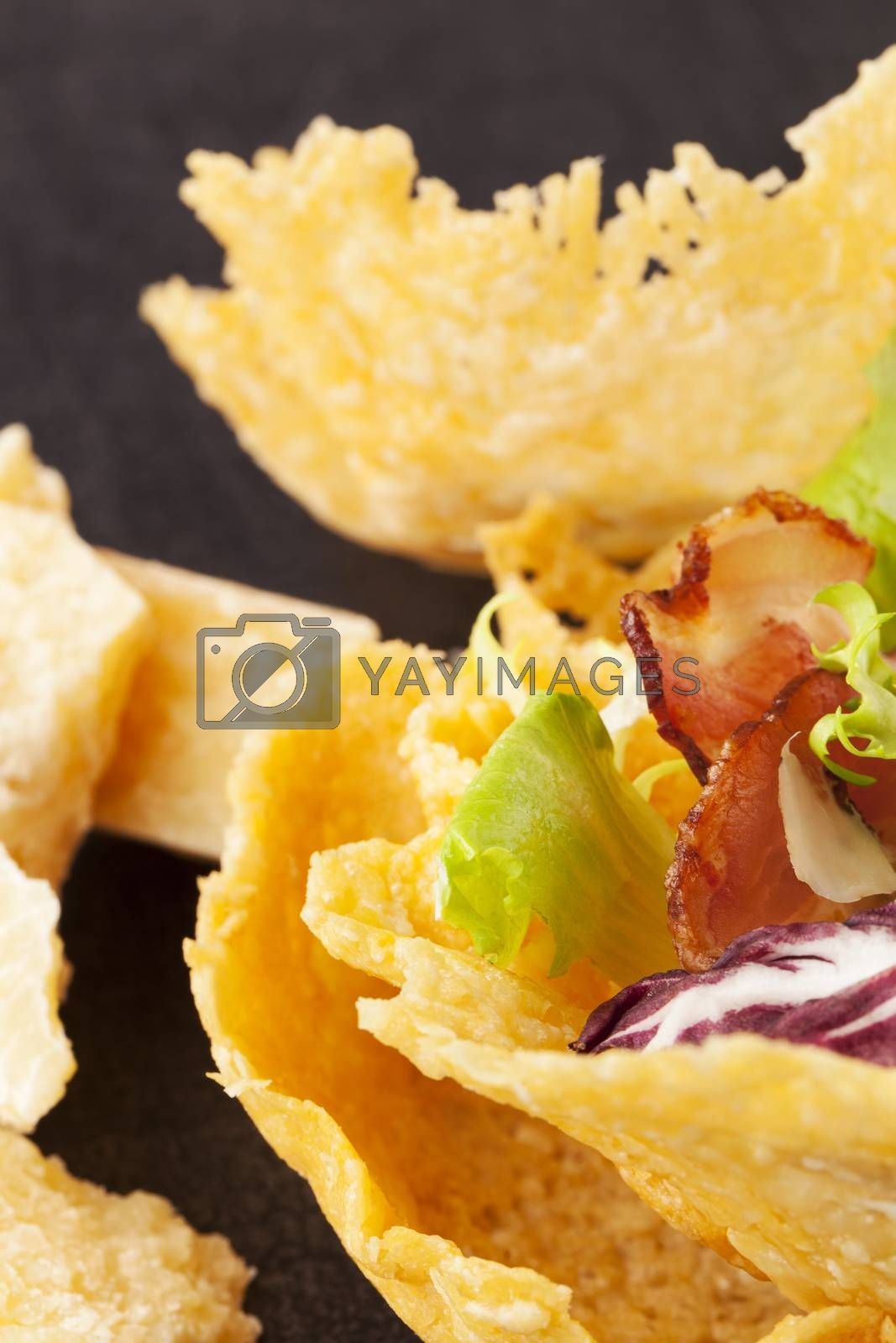 Parmigiano cheese basket filled with colorful vegetable and bacon. Luxurious cheese eating.