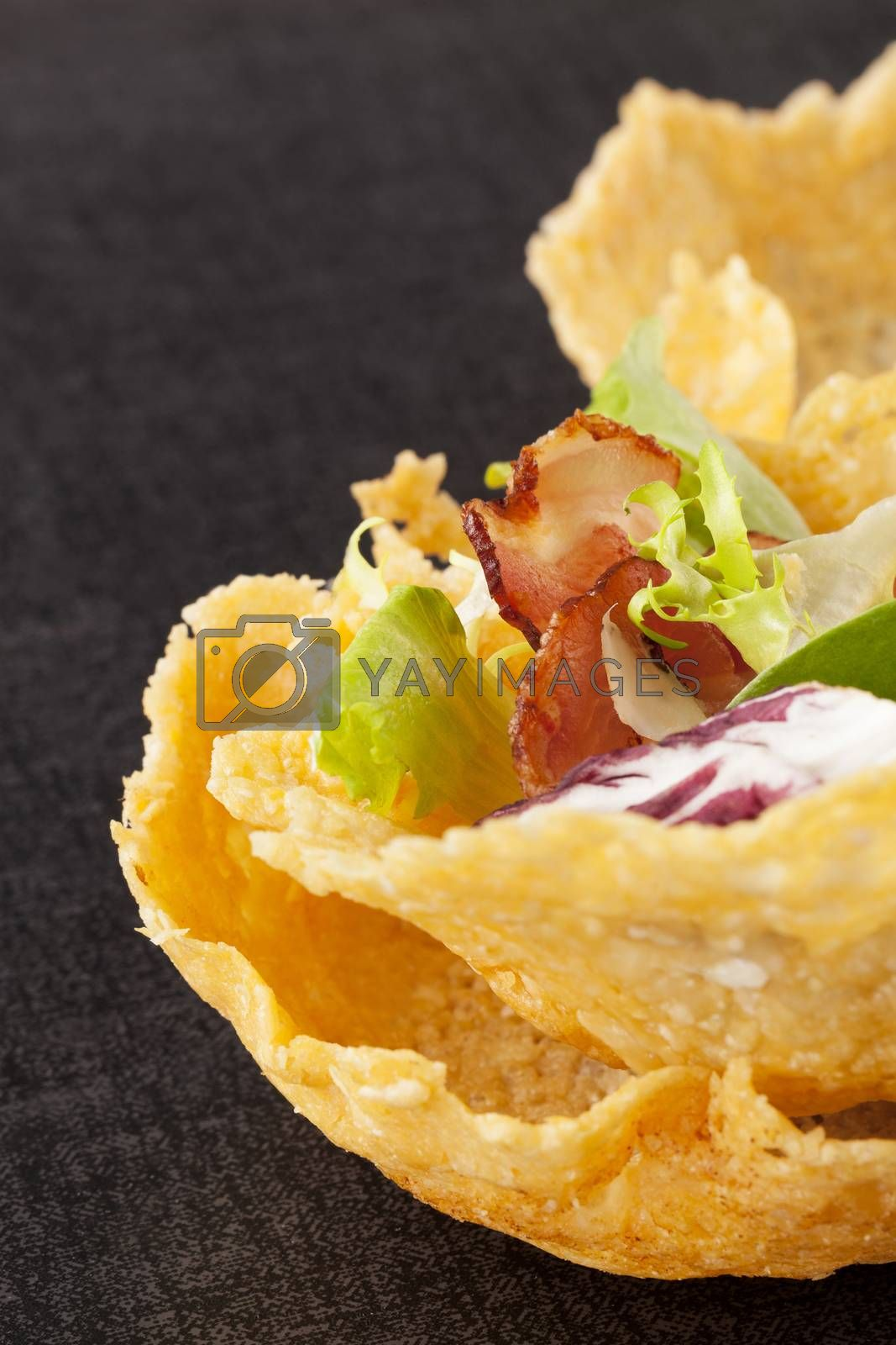 Cheese basket filled with fresh vegetable and bacon on black background. Culinary luxurious cheese eating.
