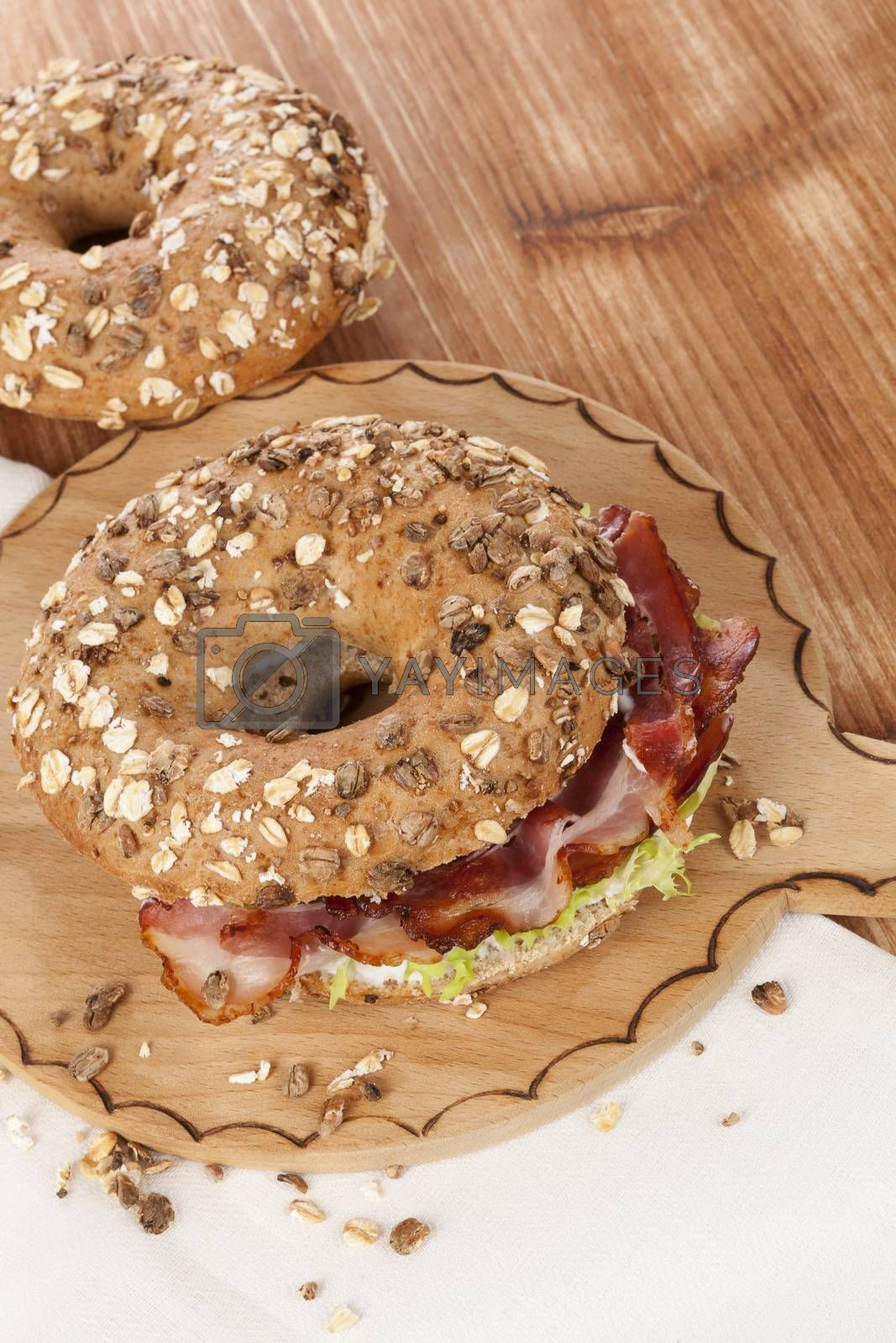 Delicious bagel eating. Whole grain bagel with bacon on wooden background.