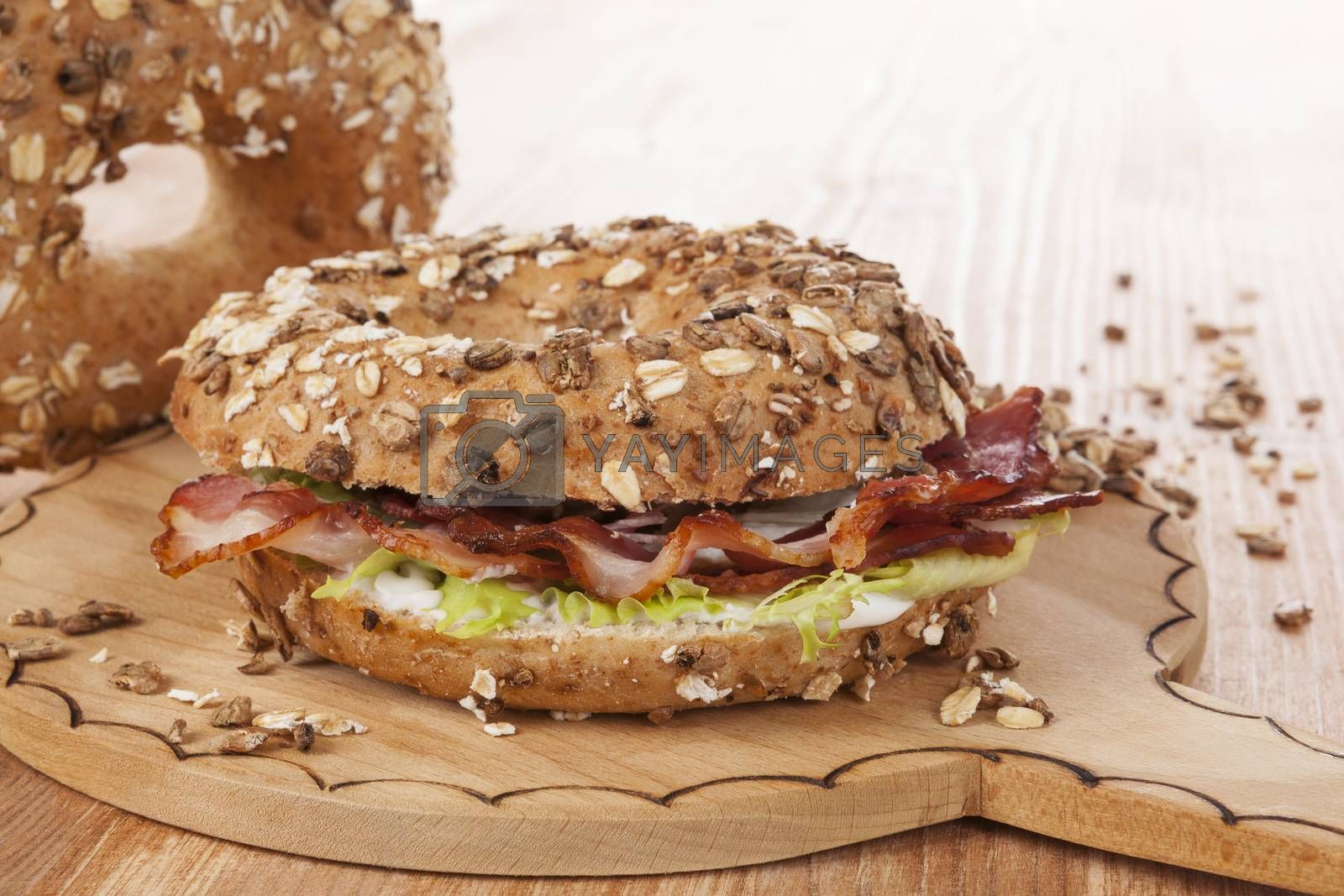 Whole grain bagel with bacon on wooden kitchen board on wooden background. Traditional bagel eating.