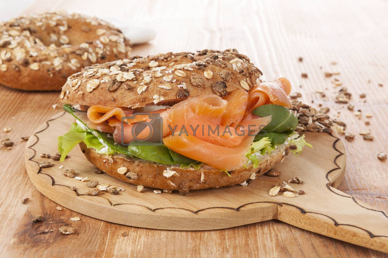 Salmon whole grain bagel on wooden kitchen board on wooden background. Traditional bagel eating.