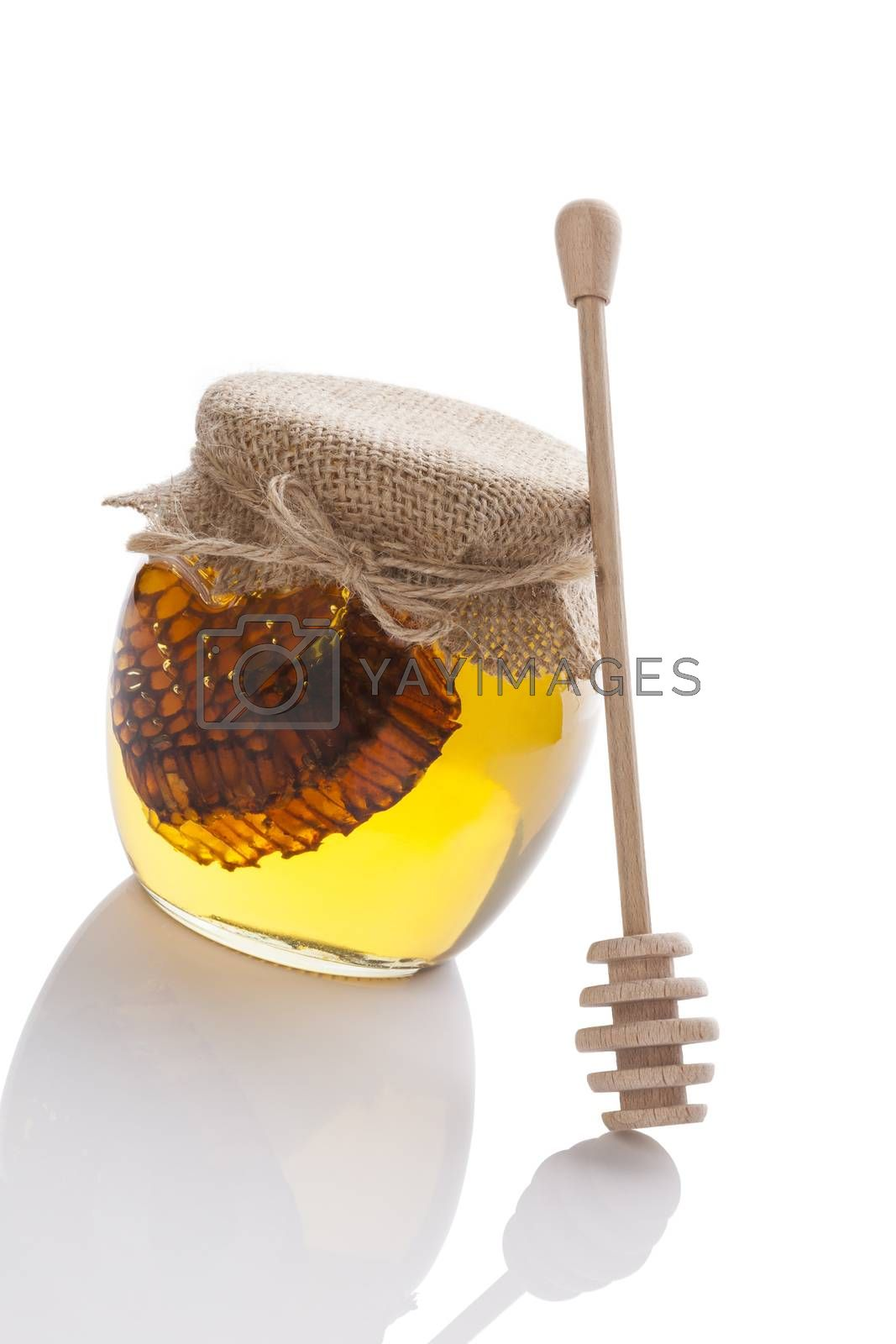 Golden honey with bee comb and wooden drizzler isolated on white background. Organic healthy natural sweetener.