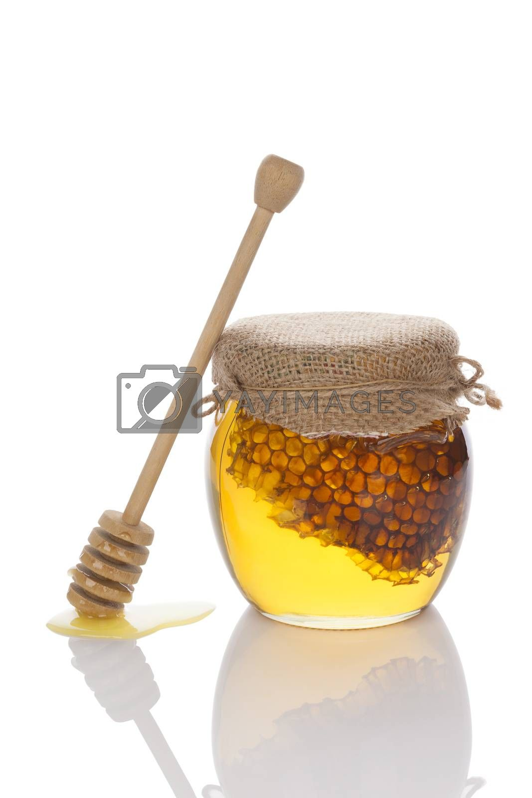 Organic bee honey in glass jar isolated on white background with wooden honey spoon. Healthy alternative medicine.