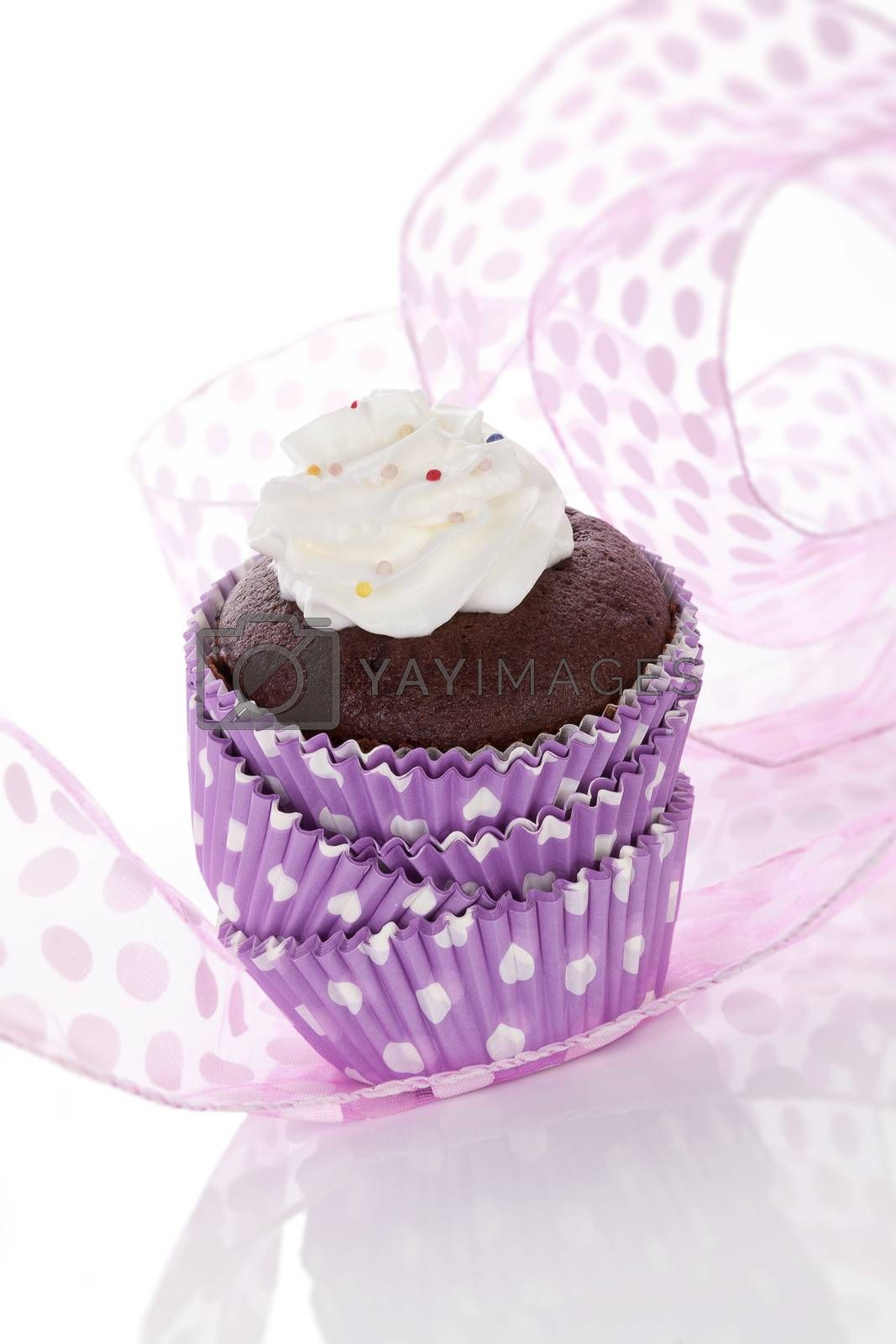 Cupcake. Delicious chocolate cupcake with whipped cream and colorful sprinkles isolated on white background. Contemporary baking concept.