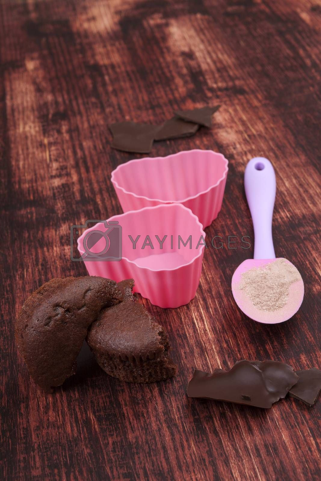 Chocolate muffin, chocolate bar, baking form and baking mixtures on brown wooden background.
