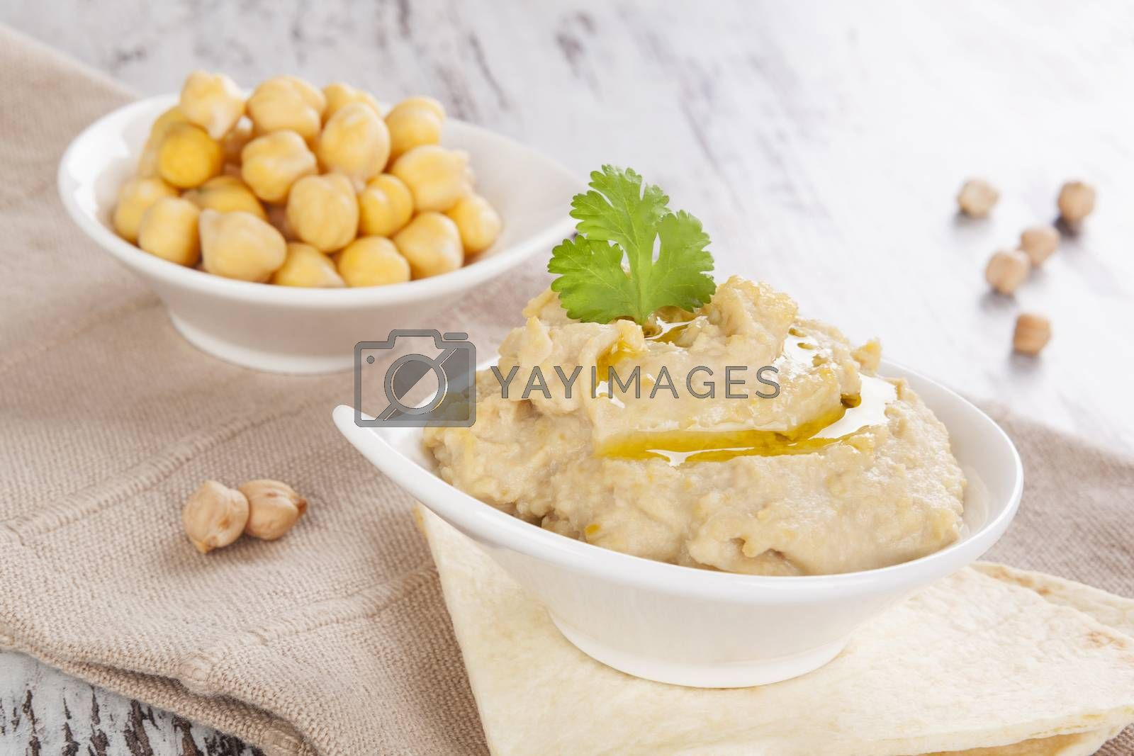 Delicious hummus and cooked chickpeas in bowl on white wooden background. Culinary hummus eating, mediterranean rustic style.