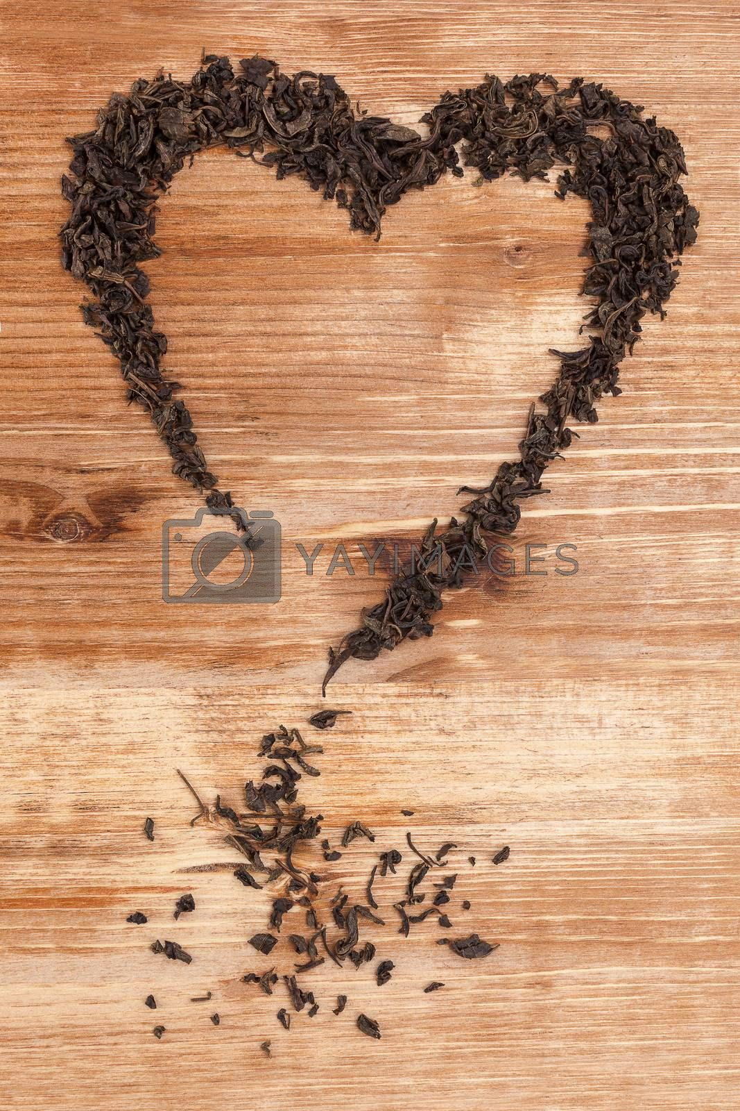 Organic dried green tea leaves in heart shape on wooden background. Traditional oriental beverage.