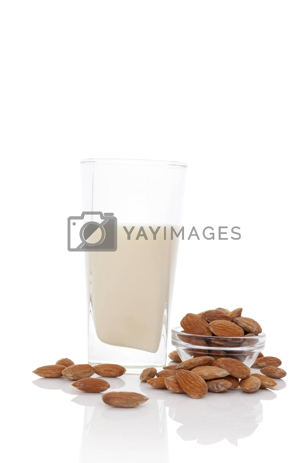Almond milk in glass with almond nuts in glass bowl isolated on white. Vegan eating concept.