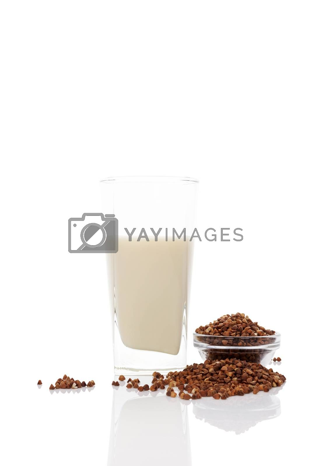 Buckwheat milk in glass with dry buckwheat seeds in glass bowl isolated on white background. Vegan and vegetarian milk concept.