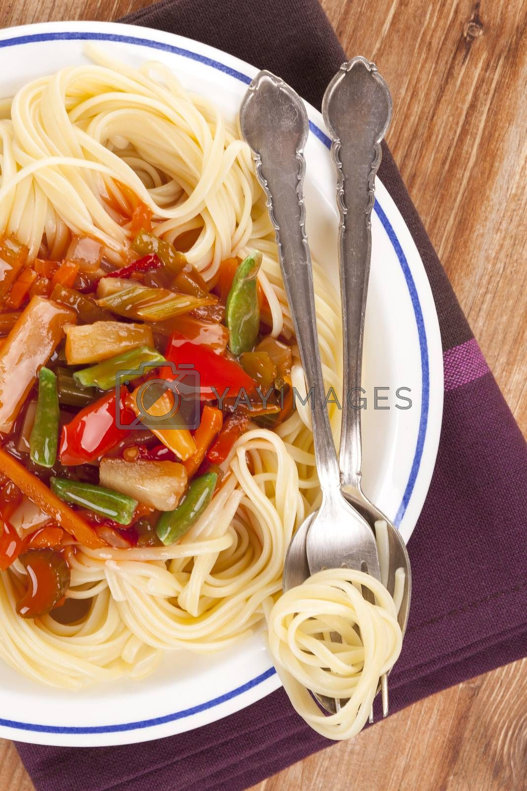 Culinary pasta eating. Pasta with tomato vegetable sauce on plate with cutlery on wooden background, top view.