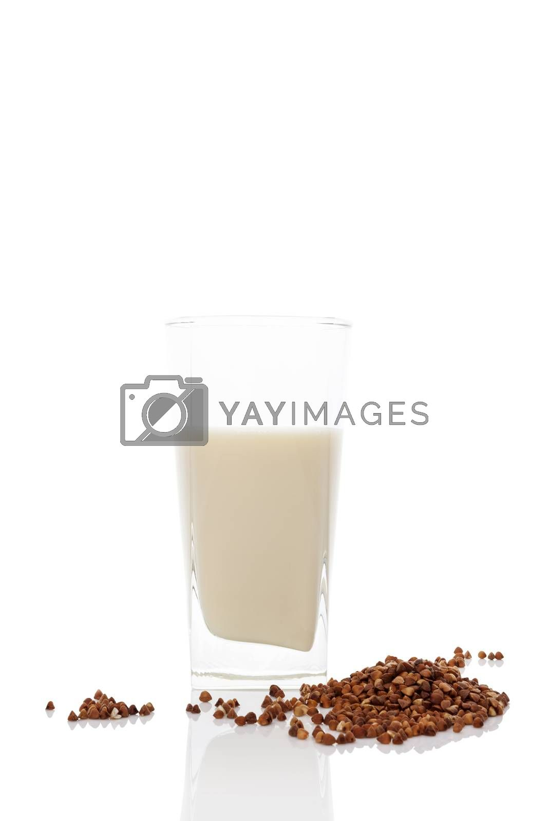 Buckwheat milk in glass with dry buckwheat seeds isolated on white background. Vegan and vegetarian milk concept.