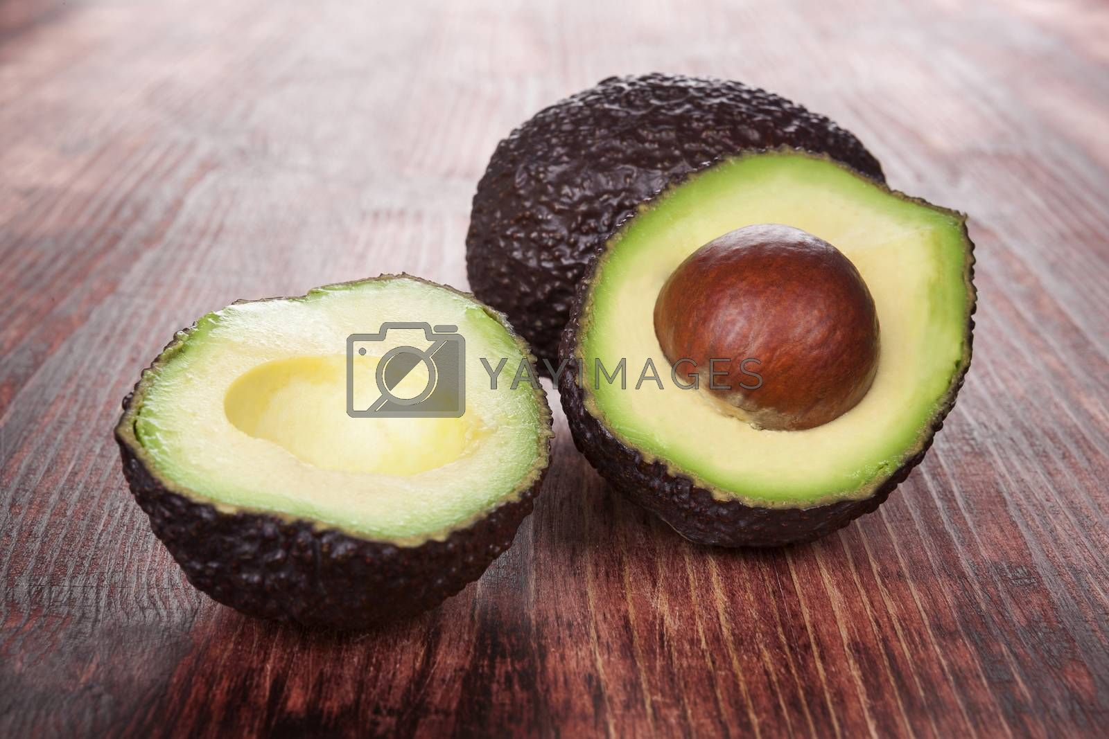 Ripe avocado on wooden background. Culinary healthy fruit eating.
