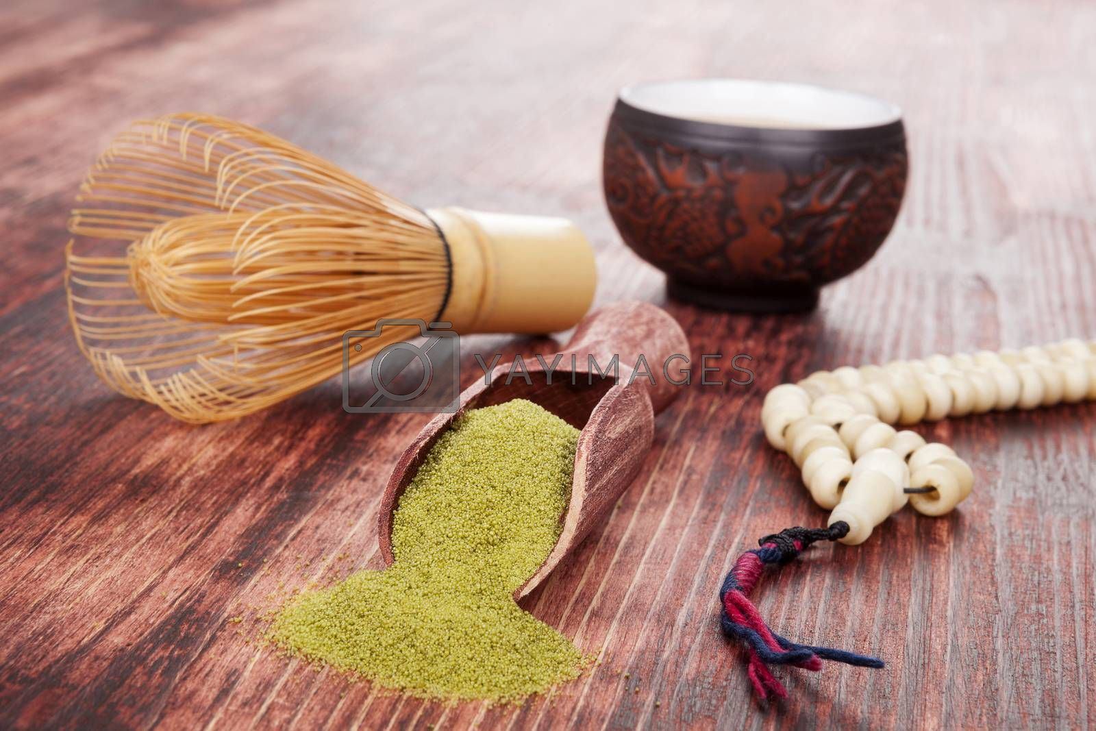 Traditional tea ceremony. Powdered green tea matcha, hot tea in ceramic cup, bamboo chasen and buddhist necklace on brown wooden background.