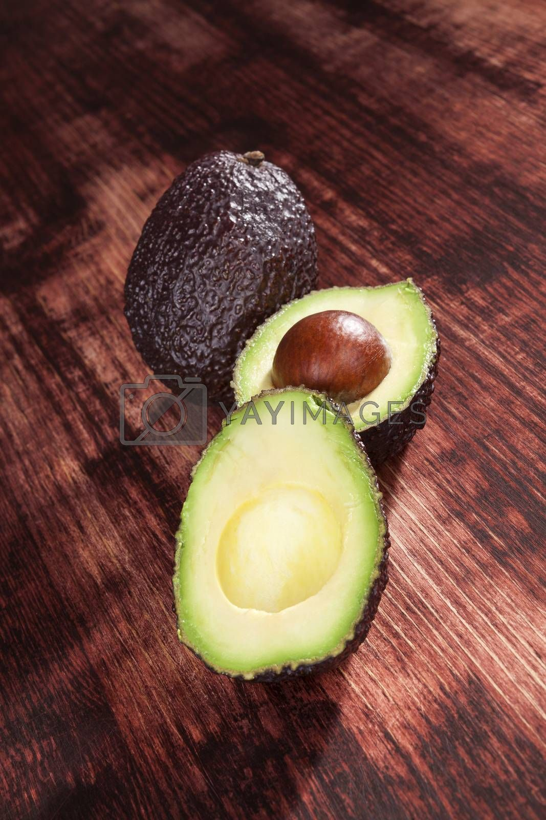 Perfect ripe cut avocados on wooden background. Culinary healthy eating.