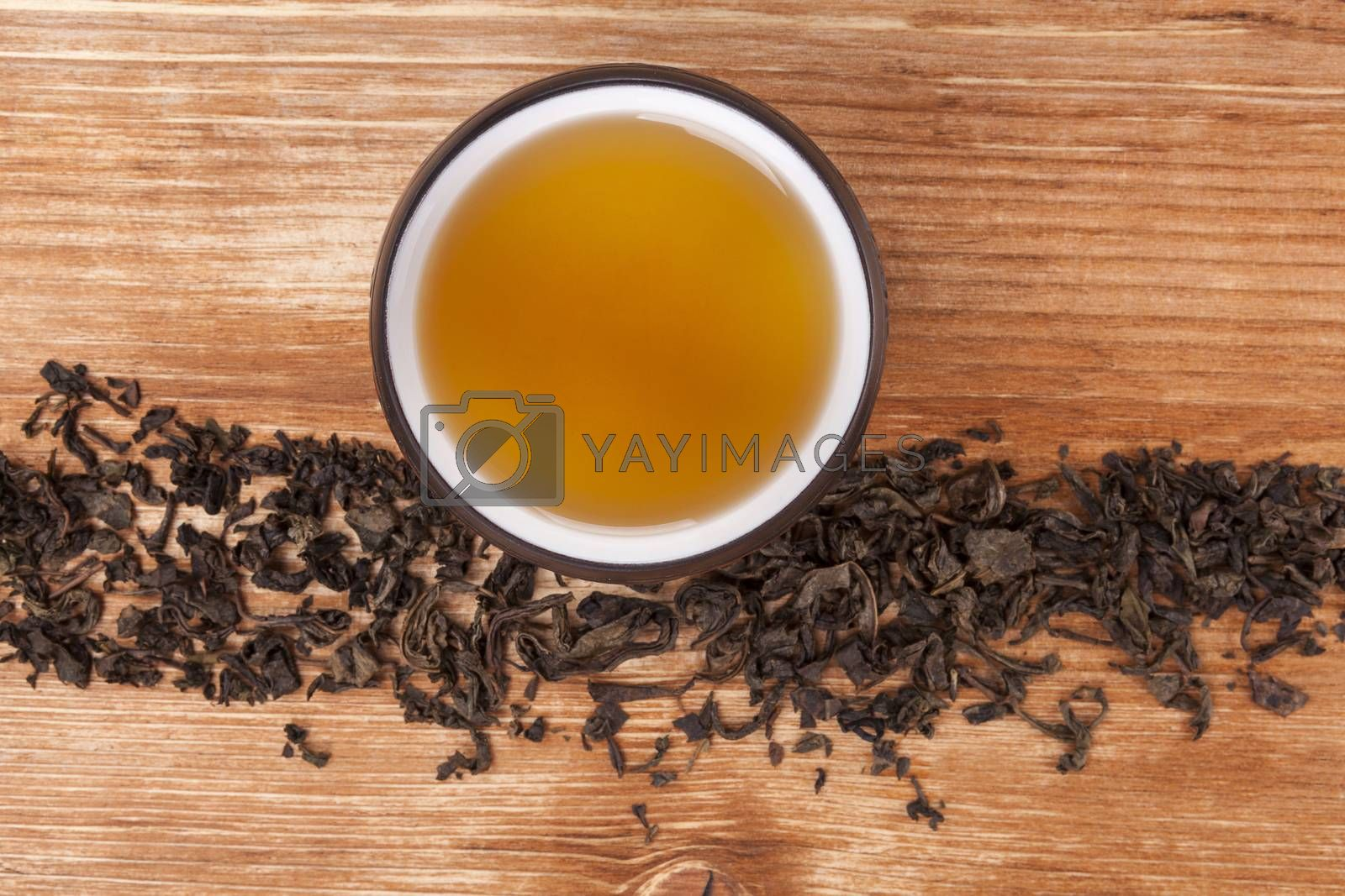Dry tea leaves and dry green tea in cup on brown wooden background, top view. Healthy alternative medicine. Traditional tea drinking.