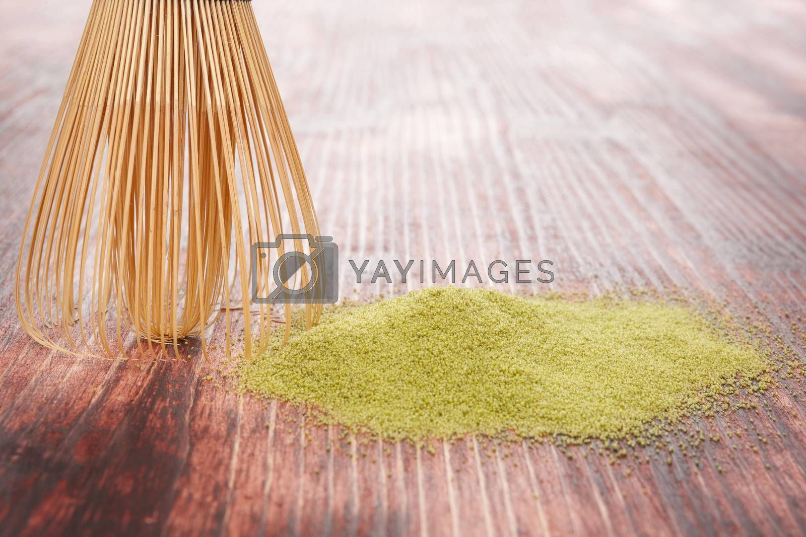 Traditional green powdered tea matcha on wooden background with bamboo chasen. Traditional japanese matcha tea ceremony.