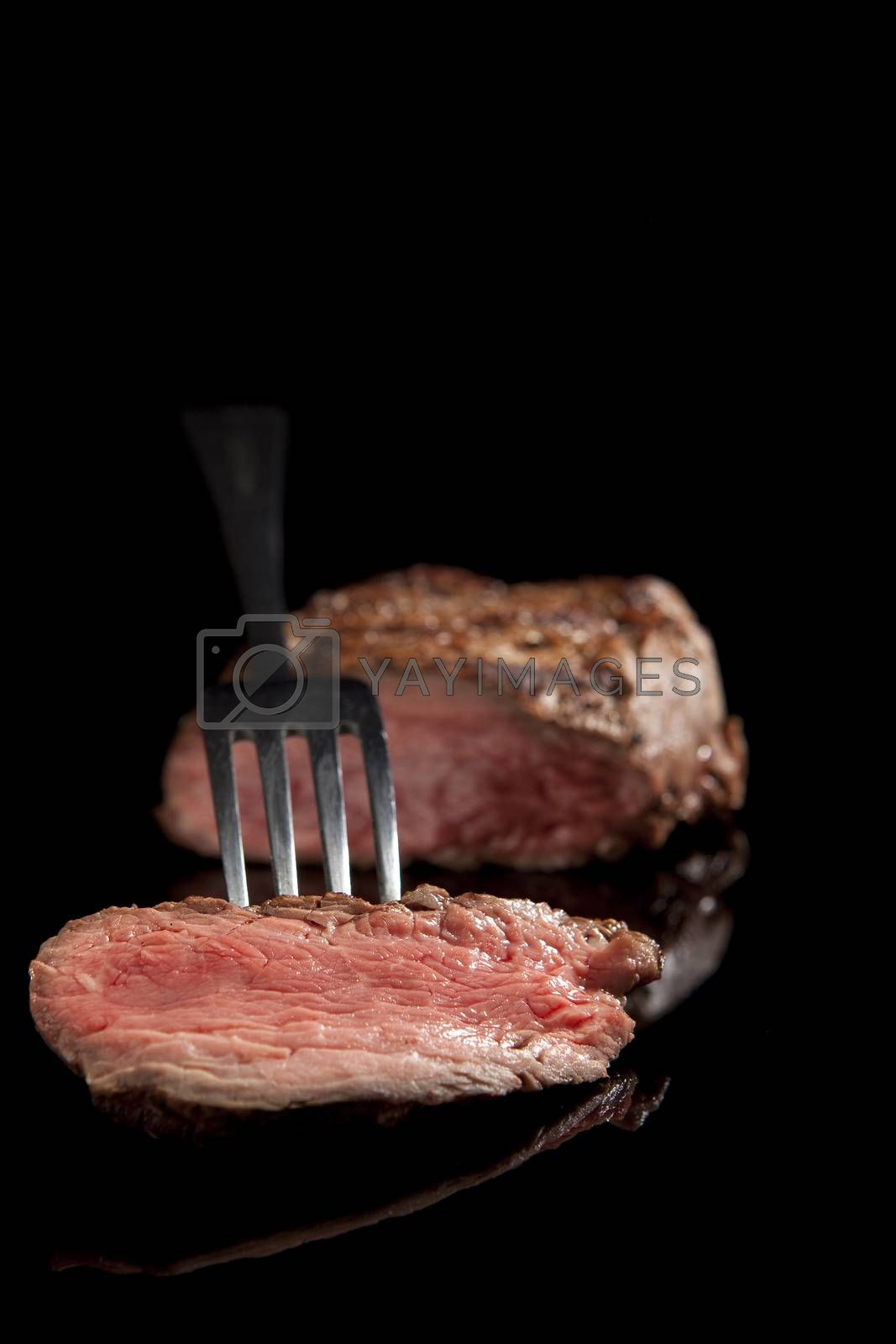 delicious medium rare sliced steak with fork